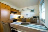 Esstisch und Küchenzeile im Hintergrund