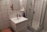 Badezimmer mit Waschbecken, WC, Dusche und Fön