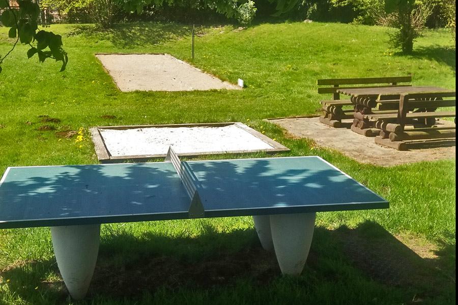 der Spielplatz mit Tischtennisplatte, Sandkasten, Boulebahn und Sitzplatz für die Eltern